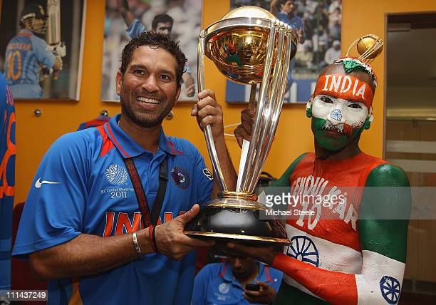 Sachin Tendulkar of India poses with the World Cup trophy and Sudhir Kumar Gautam die hard cricket fan during the 2011 ICC World Cup Final between...