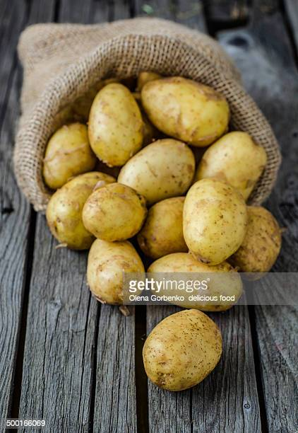 A sack of organic potatoes on wooden background