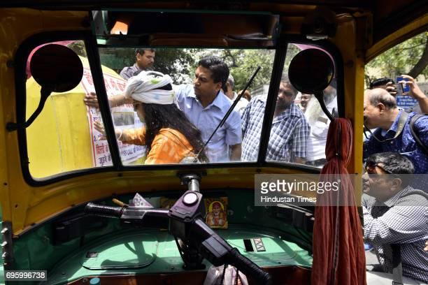 Sacked Delhi Minister Kapil Mishra pasting poster on an autorickshaw stating that Delhi Chief Minister Arvind Kejriwal cheated on autodrivers at Gole...