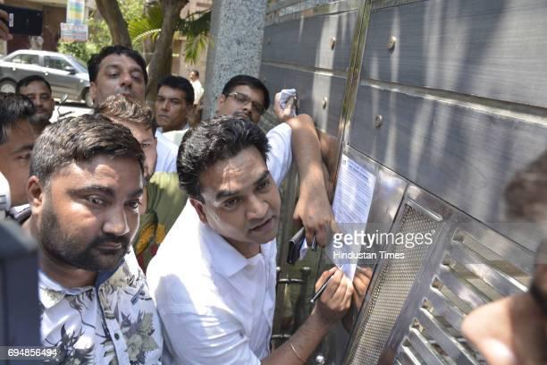 Sacked Delhi Minister Kapil Mishra putting Satyendra Jain's scam letter during a protest outside AAP leader Kumar Vishwas's residence at Vasundhra...