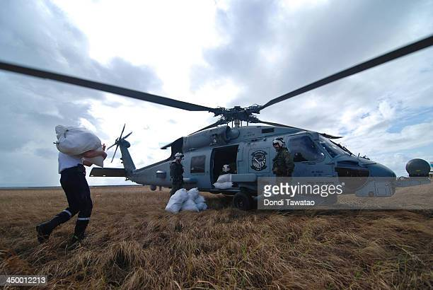 Sacks of relief goods are loaded on a US Blackhawk helicopter on November 16 2013 in Leyte Philippines Typhoon Haiyan which ripped through...