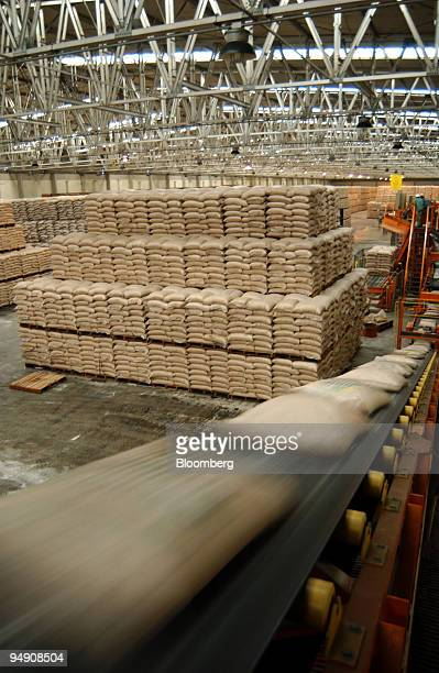Sacks of sugar are moved on a conveyor belt in a warehouse prior to loading onto cargo ships at the port of Santos Brazil on Friday February 6 2004