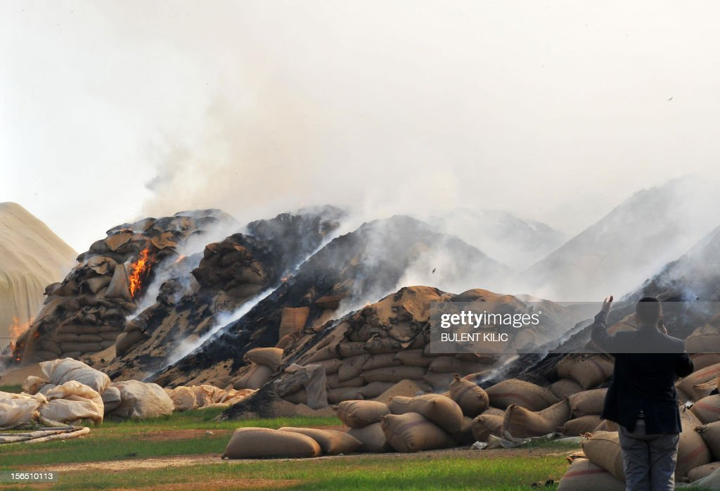 Sacks of wheat burn following air strikes by Syrian regime forces in the town of Ras al-Ain near the border with Turkey on November 16, 2012. France raised the prospect of providing Syria's rebels with defensive weapons as Turkey joined it and the Gulf Arab states in recognising the newly unified opposition while fighting raged inside Syria. AFP PHOTO/BULENT KILIC