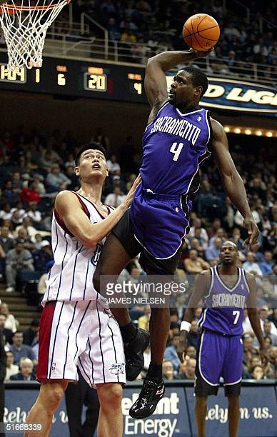 Sacramento Kings' Chris Webber glides past Houston Rockets' Yao Ming in the first quarter at the Compaq Center 10 December 2002 in Houston Texas AFP...
