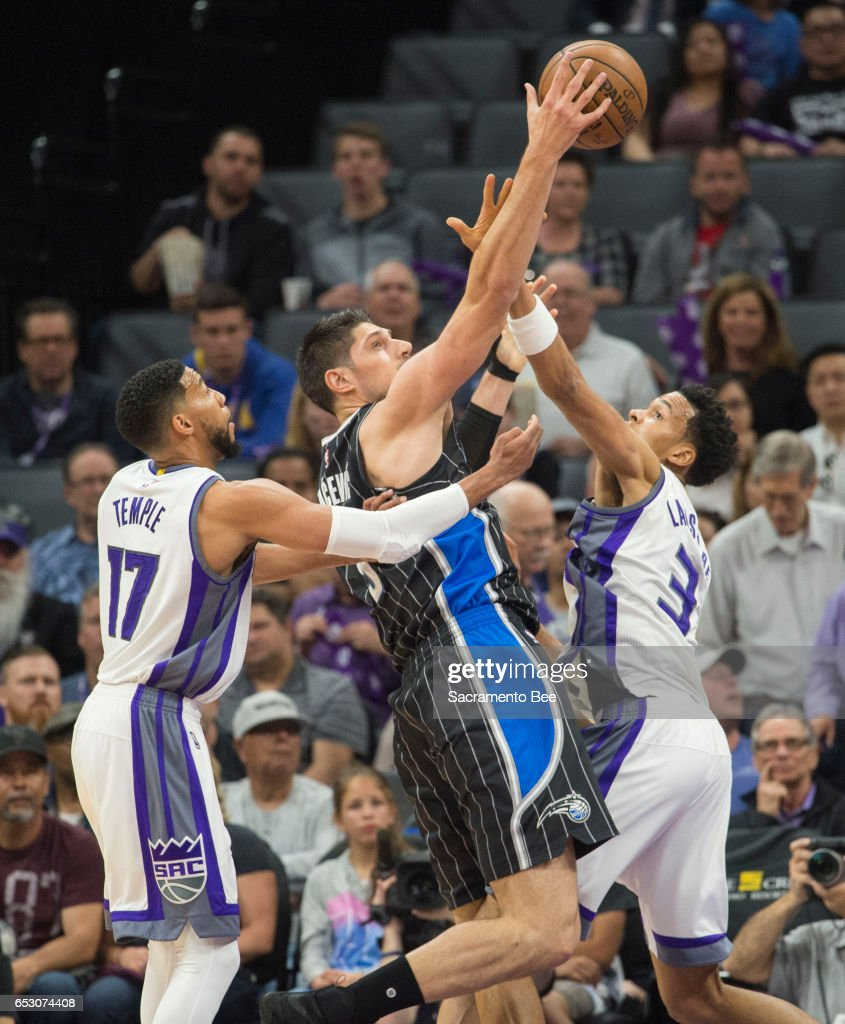 Sacramento Kings guard Garrett Temple (17) and forward Skal Labissiere (3) defend Orlando Magic center Nikola Vucevic (9) on Monday, March 13, 2017 at Golden 1 Center in Sacramento, Calif.