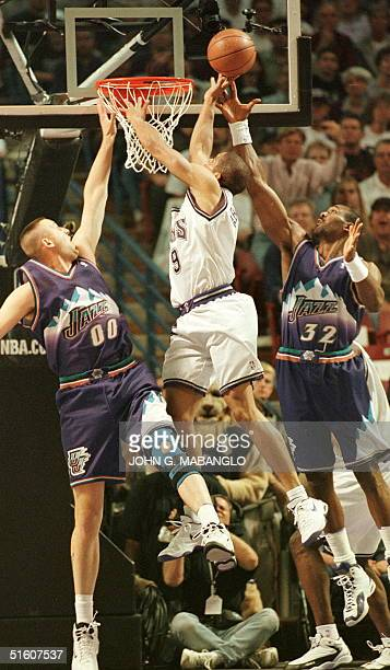 Sacramento Kings Tariq AbdulWahad of France goes up for a rebound against Utah Jazz Karl Malone and Jazz Greg Ostertag in the fourth game of their...