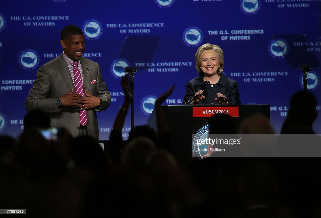 Sacramento mayor <a gi-track='captionPersonalityLinkClicked' href=/galleries/search?phrase=Kevin+Johnson+-+Politician&family=editorial&specificpeople=12777886 ng-click='$event.stopPropagation()'>Kevin Johnson</a> (L) looks on as democratic presidential candidate and former U.S. Secretary of State <a gi-track='captionPersonalityLinkClicked' href=/galleries/search?phrase=Hillary+Clinton&family=editorial&specificpeople=76480 ng-click='$event.stopPropagation()'>Hillary Clinton</a> prepares to speak during the 2015 United States Conference of Mayors on June 20, 2015 in San Francisco, California. The 83rd Annual Meeting of the U.S. Conference of Mayors runs through June 22.