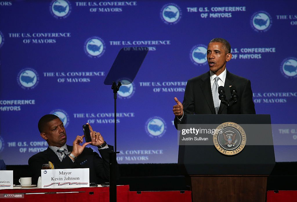 Sacramento mayor Kevin Johnson takes a picture of US President Barack Obama as he speaks during the 2015 United States Conference of Mayors on May 19...