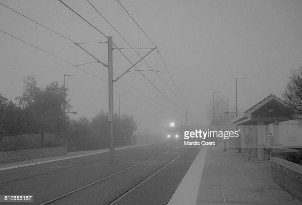 A Sacramento Regional Transit Light Rail train arriving at one of its stations and in an early morning fog