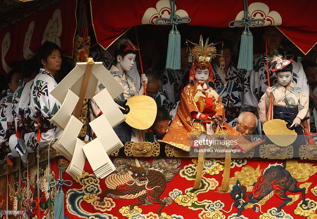 A sacred child (C) performs a ritual on a float named Yamahoko during the annual Kyoto Gion Festival on July 17, 2013 in Kyoto, Japan. The Gion festival is one of three biggest Japanese festivals. dating back to the 9th century, the festival is part of a ritual intended to satisfy the Gods that brought on fire, floods and earthquakes. During the festival the streets are decorated with lanterns and many of the women dress in 'yukata', summer kimonos.