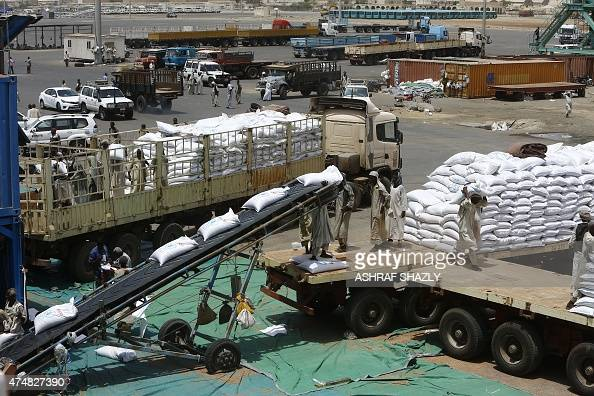 Sacs of sorghum are unloaded from US vessel Liberty Grace hired by the World Food Program to deliver aid food donated from USAID to people in Sudan's...