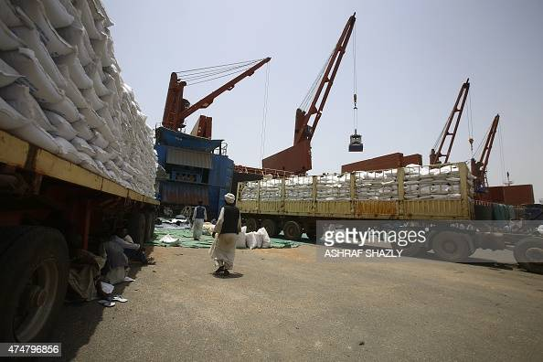 Sacs of sorghum pile on lorries after it was unloaded from US vessel Liberty Grace hired by the World Food Program to deliver aid food from USAID...