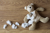 A sad, children's teddy Bear with its stuffing torn and scattered over a wooden floor.