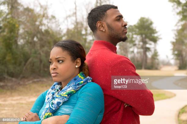 Sad African descent couple in park setting after argument.