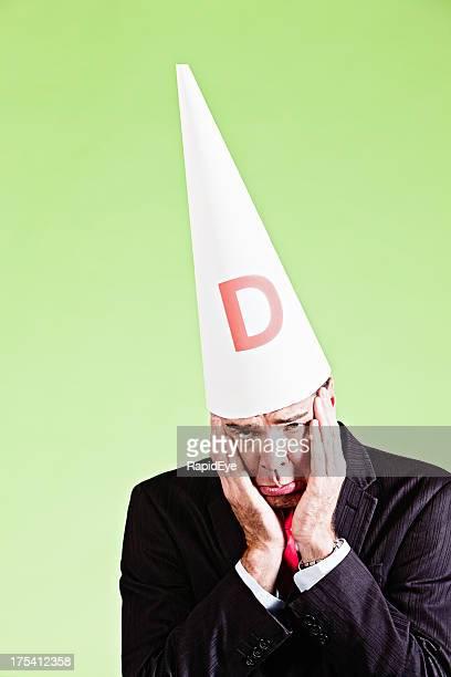 Sad ashamed businessman in dunce cap is sorry