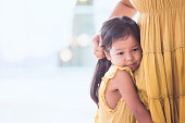 Sad asian child girl hugging her mother leg in vintage color tone