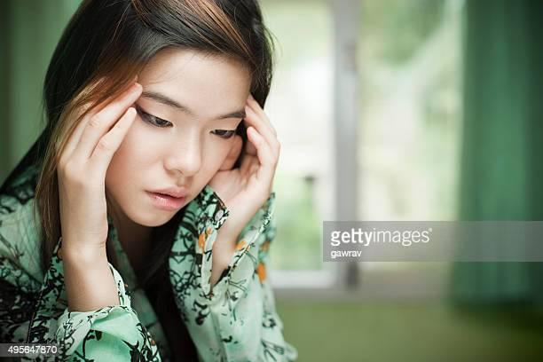 Sad Asian cute girl sitting near window holding her head.