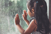 Sad asian little girl looking outside through the window in the rainy day in vintage color tone
