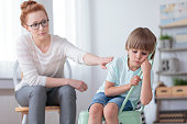 Sad autistic boy sitting on mint chair during session with red haired psychotherapist