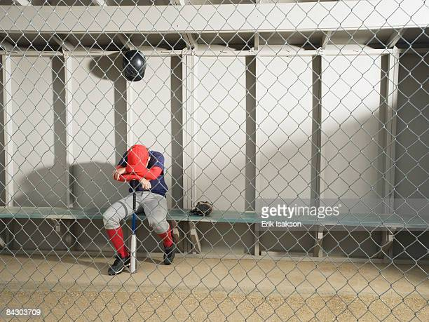 Sad baseball player sitting in dugout