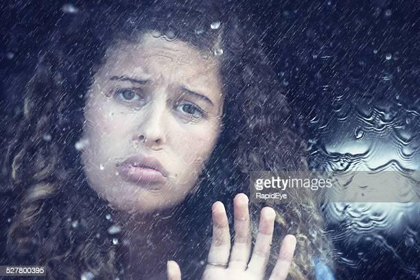 Sad beauty looking through rain-streaked window, depressed