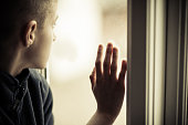 Close up Lonely Orphan Boy in an Orphanage Looking Outside While Holding the Glass Window.