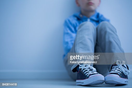 Sad boy sits alone : Stock Photo