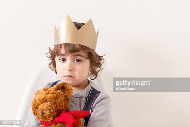 Sad boy wearing paper crown