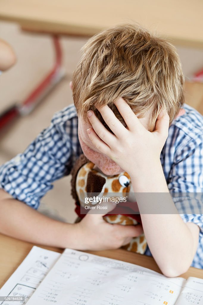 Sad boy with stuffed animal studying : Foto stock