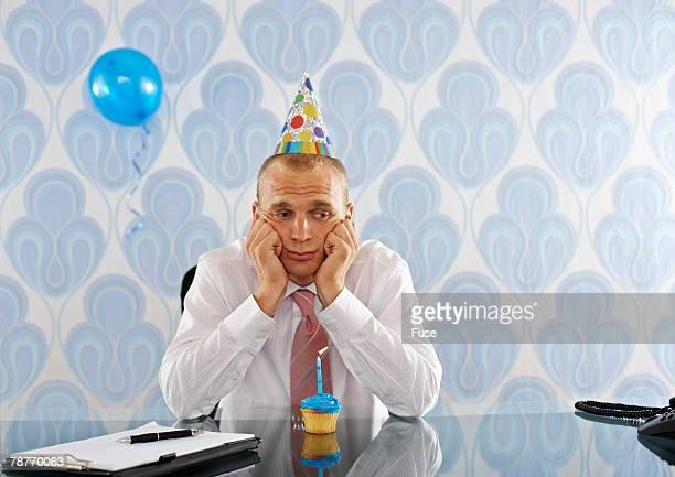 Sad Businessman at Desk Wearing Party Hat