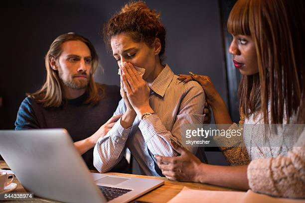 Sad businesswoman crying while her colleagues are consoling her.