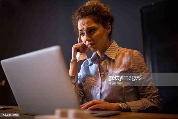 Sad businesswoman in the office working on laptop.