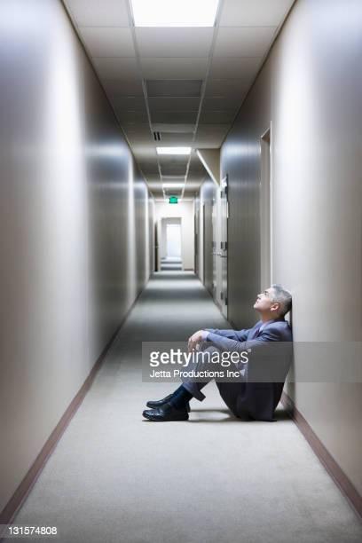 Sad Caucasian businessman sitting on floor in office corridor