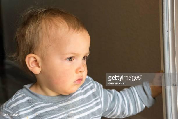 Sad child looking through a window