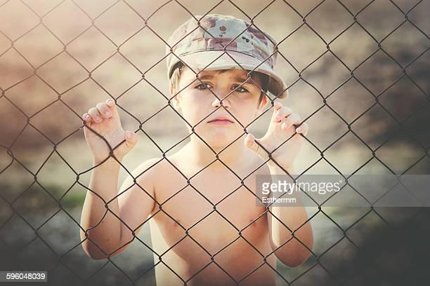 Sad child next to a fence