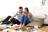 Sad couple calling to police sitting on the floor of the messy living room after home robbery