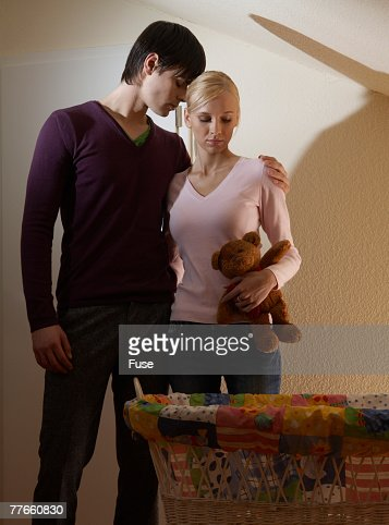 Sad Couple Looking at Bassinet