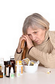 portrait of a sad elderly woman looks at medicine on a white background