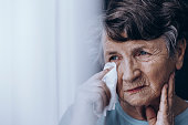 Sad elderly woman wiping tears with tissue while standing alone in house