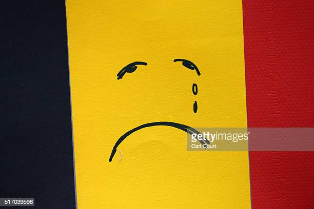 A sad face is drawn on a Belgian flag near Maelbeek metro station following yesterday's attack on March 23 2016 in Brussels Belgium Belgium is...