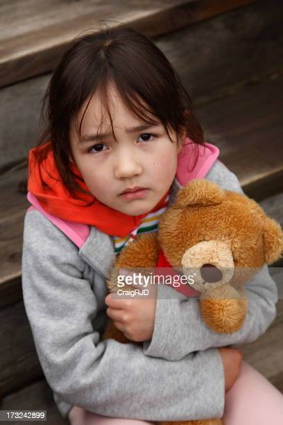 Sad female child holding bear dressed in rags