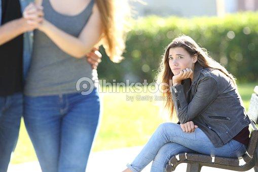 Sad girl looking at a couple walking : Stock Photo