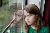 Young, brunette girl is looking out the window with a sad face, and her image is reflecting in the glass