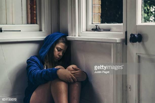 Sad Girl sat in corner of room