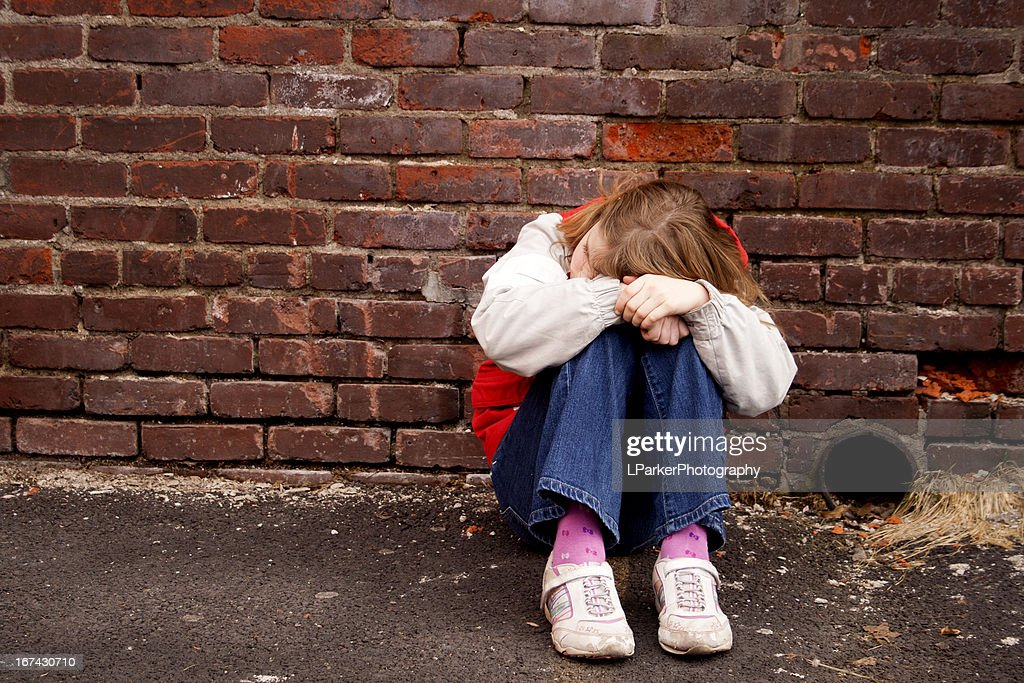 Sad girl sitting against a brick wall : Stock Photo