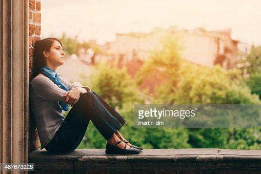 Sad girl sitting thoughtfully outside