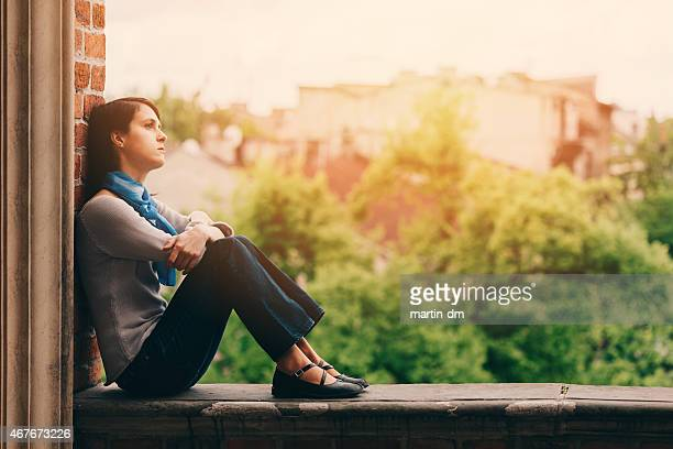Sad girl sitting thoughtfully outside