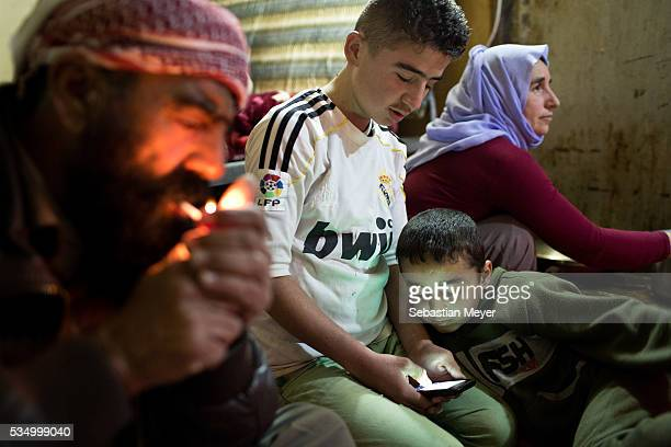 Saïd lights a cigarette while Ezidiar looks at Serdesht's phone and Ghazal watches television The family of Yezidis displaced from Sinjar live next...