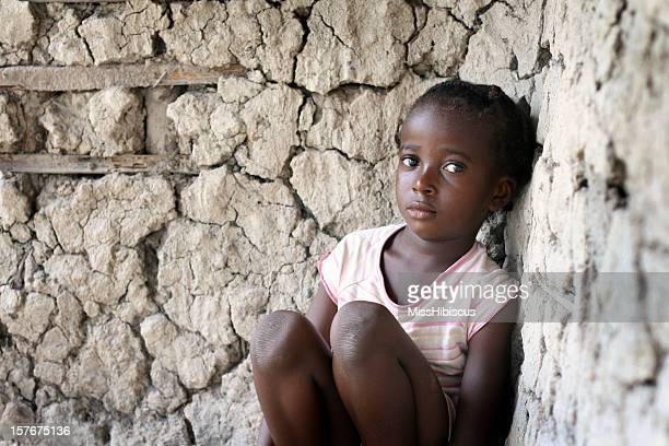 Sad little African girl, sitting against a wall