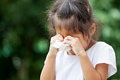 Sad little asian girl crying and holding tissue on her hand
